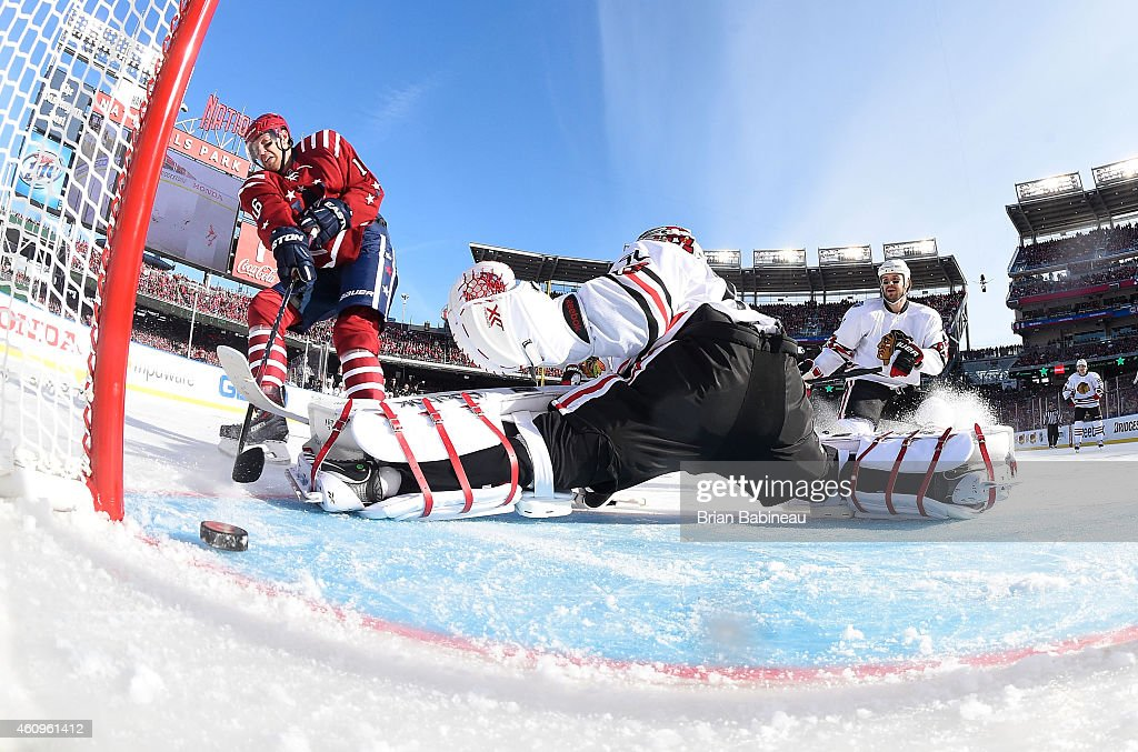Eric Fehr #16 of the Washington Capitals slides a shot past goaltender Corey Crawford #50 of the Chicago Blackhawks in the first period during the 2015 Bridgestone NHL Winter Classic at Nationals Park on January 1, 2015 in Washington, D.C. Fehr scored on the play.