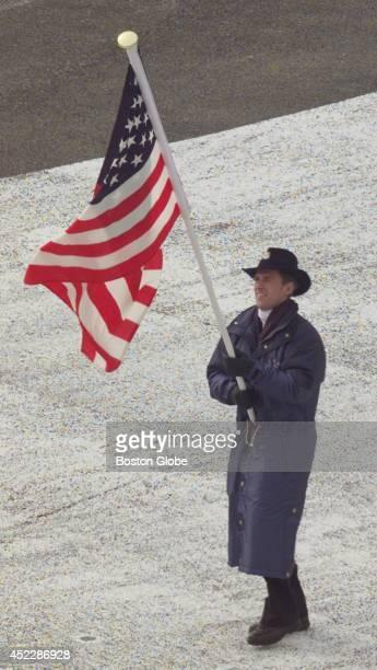 Eric Flaim carries the flag into Olympic Stadium ahead of the US team