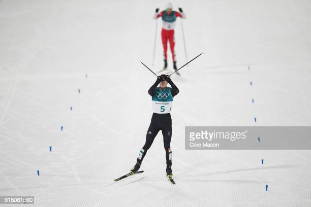 Eric Frenzel of Germany celebrates as he crosses the line to win gold ahead of Akito Watabe of Japan during the Nordic Combined Individual Gundersen...
