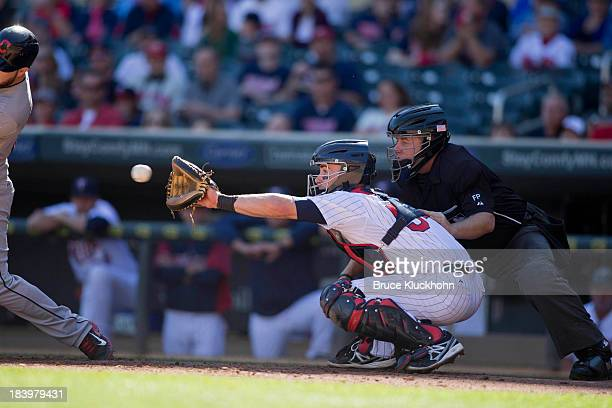 Eric Fryer of the Minnesota Twins catches a pitch during the game against the Cleveland Indians as umpire Greg Gibson watches on September 29 2013 at...