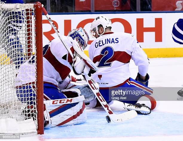 Eric Gelinas helps goalie Zachary Fucale of the Laval Rocket make a save against the of the Toronto Marlies during AHL game action on March 12 2018...