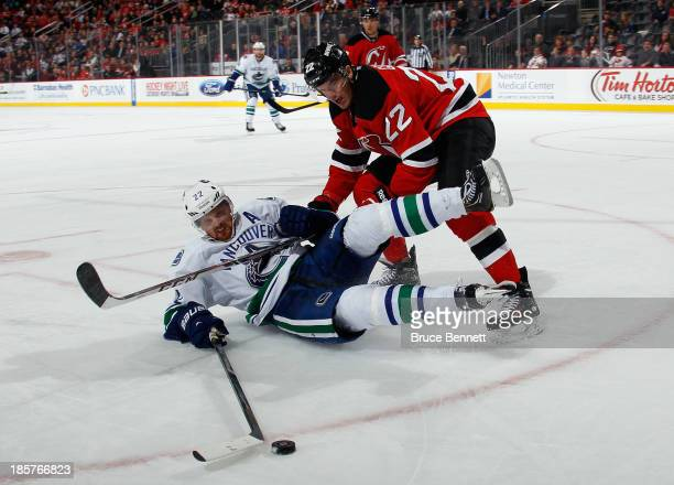 Eric Gelinas of the New Jersey Devils dumps Daniel Sedin of the Vancouver Canucks during the third period at the Prudential Center on October 24 2013...