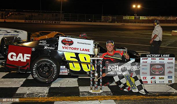 Eric Goodale driver of the GAF Roofing/RBSCorpcom celebrates after winning the Hoosier Tire 200 at Riverhead Raceway on June 28 2014 in Riverhead New...