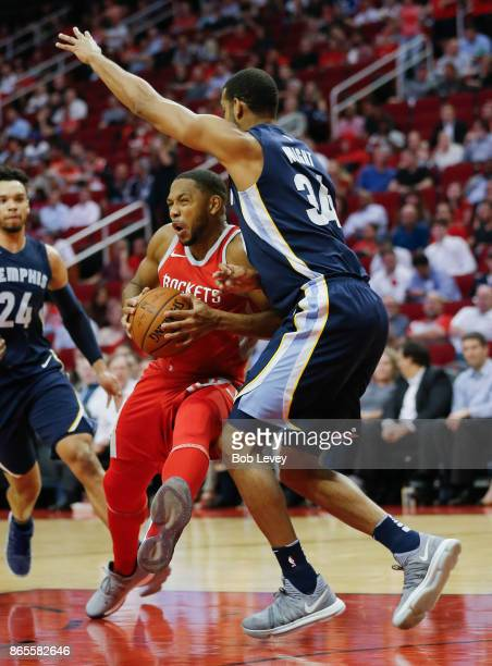 Eric Gordon of the Houston Rockets attempts to drive around Brandan Wright of the Memphis Grizzlies at Toyota Center on October 23 2017 in Houston...