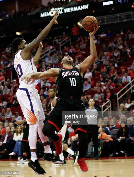 Eric Gordon of the Houston Rockets drives around Troy Daniels of the Phoenix Suns in the second half at Toyota Center on January 28 2018 in Houston...