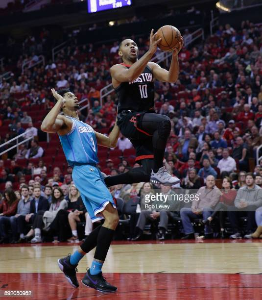 Eric Gordon of the Houston Rockets drives past Jeremy Lamb of the Charlotte Hornets for a layup at Toyota Center on December 13 2017 in Houston Texas...