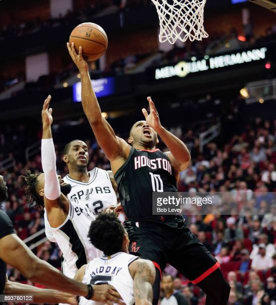 Eric Gordon of the Houston Rockets drives to the basket over Patty Mills of the San Antonio Spurs and LaMarcus Aldridge at Toyota Center on December...