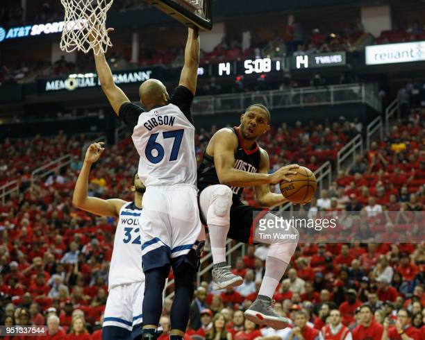 Eric Gordon of the Houston Rockets passes the ball under the basket defended by Taj Gibson of the Minnesota Timberwolves in the first half during...
