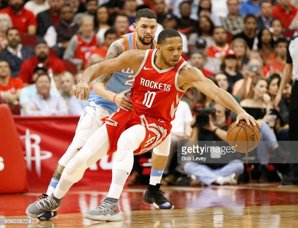 Eric Gordon of the Houston Rockets reaches for the ball as Austin Rivers of the LA Clippers looks on at Toyota Center on March 15 2018 in Houston...