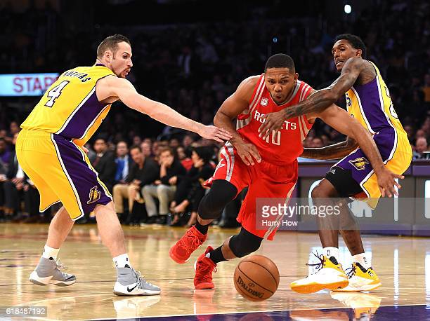 Eric Gordon of the Houston Rockets splits the defense of Marcelo Huertas and Louis Williams of the Los Angeles Lakers at Staples Center on October 26...