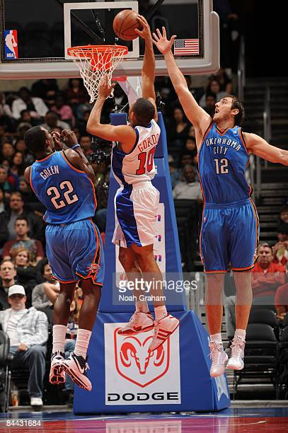 Eric Gordon of the Los Angeles Clippers goes up for a shot against Jeff Green and Nenad Krstic of the Oklahoma City Thunder at Staples Center on...