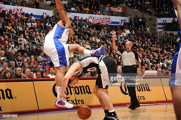 Eric Gordon of the Los Angeles Clippers loses his balance against Manu Ginobili of the San Antonio Spurs at Staples Center on December 13 2009 in Los...