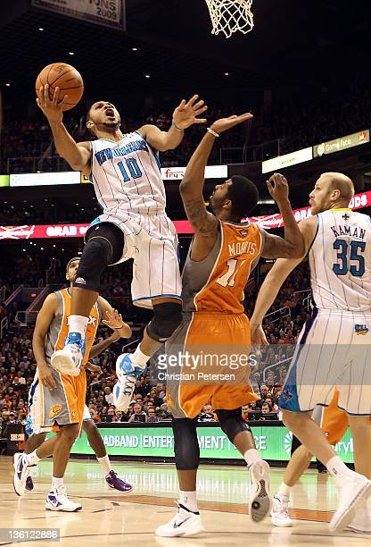 Eric Gordon of the New Orleans Hornets puts up a shot past Markieff Morris of the Phoenix Suns during the season openning NBA game at US Airways...