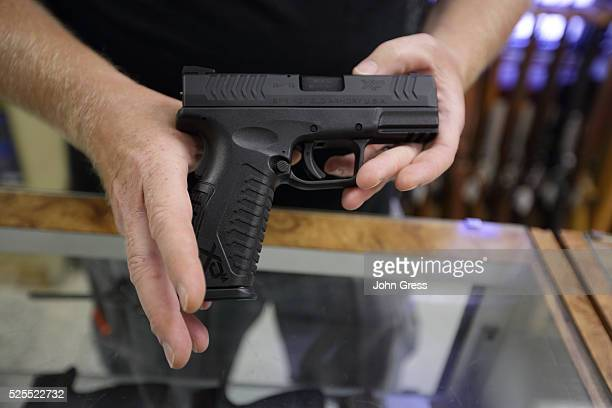 Eric Grabowski holds a hand gun, very similar to the gun used by alleged gunman Wade Michael Page at The Shooters Shop in West Allis, Wisconsin, on...