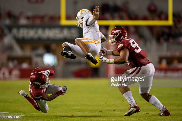 Eric Gray of the Tennessee Volunteers is tripped up in the second half by Greg Brooks Jr. #9 of the Arkansas Razorbacks at Razorback Stadium on...