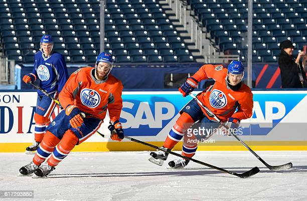 Eric Gryba and Oscar Klefbom of the Edmonton Oilers skate during warmup in advance of the 2016 Tim Hortons NHL Heritage Classic game at Investors...
