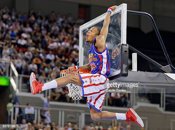 Eric 'Hacksaw' Hall of Harlem Globetrotters hangs on the backboard during the exhibition game between Harlem Globetrotters and World AllStars at...