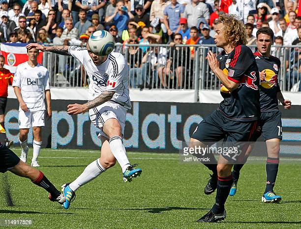 Eric Hassli of the Vancouver Whitecaps FC kicks the ball as Stephen Keel of the New York Red Bulls looks on during their MLS match May 28 2011 in...