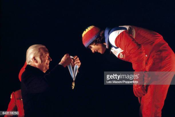 Eric Heiden of the USA bends to receive the gold medal from the International Olympic Committee President Lord Killanin after winning the men's 10000...