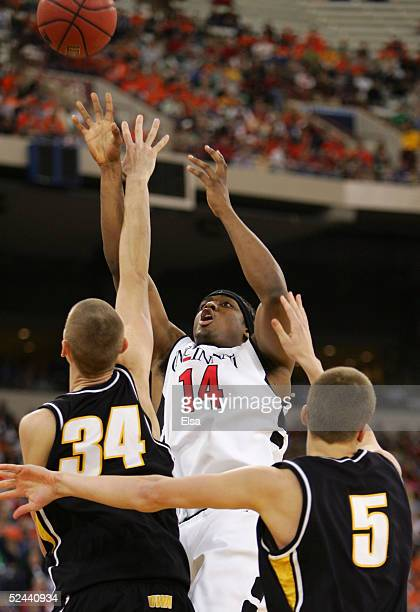 Eric Hicks of the Cincinnati Bearcats attempts a shot against Erek Hanson and AlexThompson of the Iowa Hawkeyes in the first round game of the NCAA...