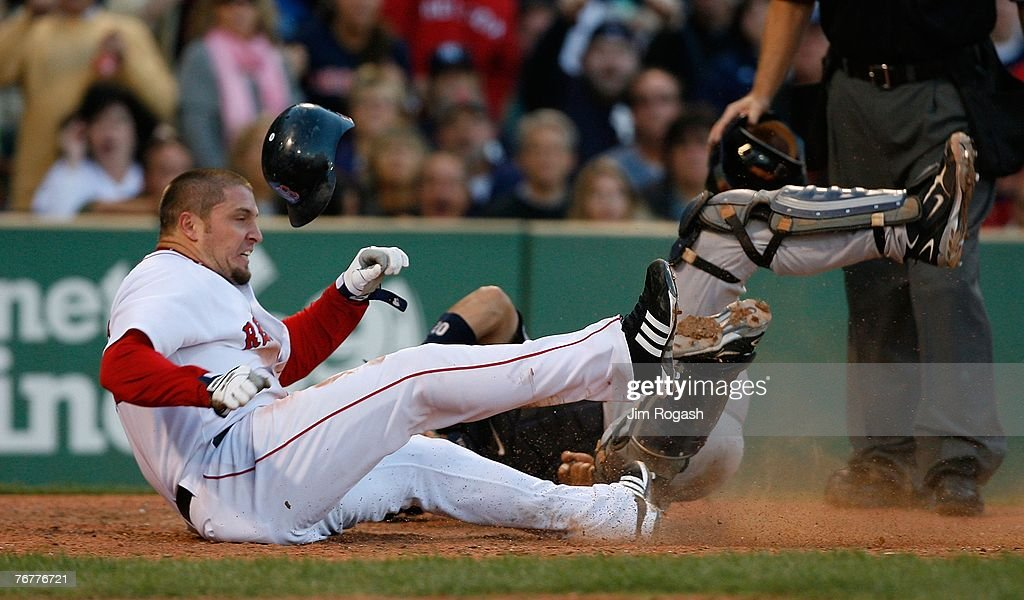 Eric Hinske #12 of the Boston Red Sox is tagged out before colliding with Jorge Posada #20 of the New York Yankees at Fenway Park, September 15, 2007 in Boston, Massachusetts.