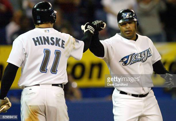 Eric Hinske of the Toronto Blue Jays congratulates teammate Vernon Wells after Wells hit a solo home run in the 8th inning against the Washington...