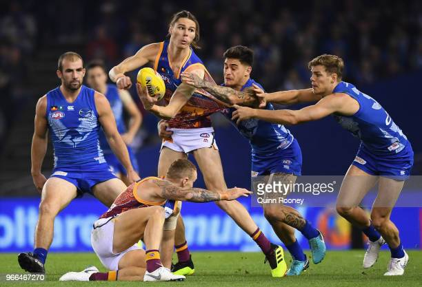 Eric Hipwood of the Lions handballs whilst being tackled by Marley Williams of the Kangaroos during the round 11 AFL match between the North...