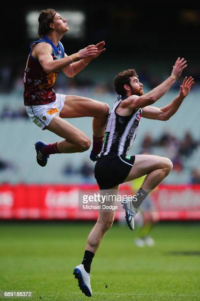 Eric Hipwood of the Lions marks the ball over Tyson Goldsack of the Magpies during the round 10 AFL match between the Collingwood Magpies and...