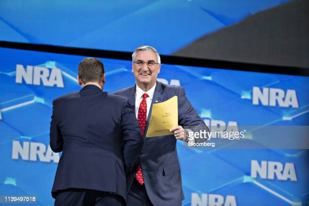 Eric Holcomb, governor of Indiana, right, arrives in stage to speak at the National Rifle Association Institute for Legislative Action Leadership...
