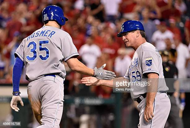 Eric Hosmer celebrates with third base coach Mike Jirschele of the Kansas City Royals after hitting a tworun home run in the elventh inning against...