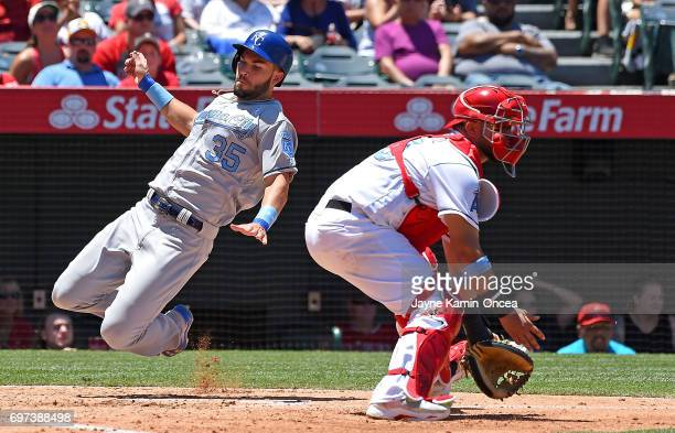 Eric Hosmer of the Kansas City Royals beats the throw to Juan Graterol of the Los Angeles Angels to score a run in the third inning at Angel Stadium...