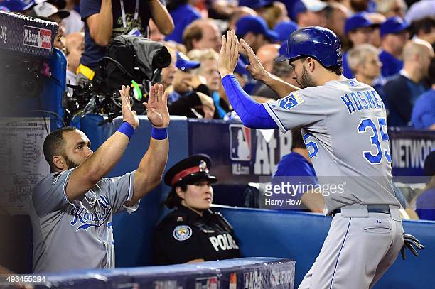 Eric Hosmer of the Kansas City Royals celebrates with Kendrys Morales of the Kansas City Royals in the dugout after scoring a run in the first inning...