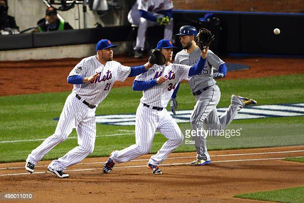 Eric Hosmer of the Kansas City Royals is safe at first as Noah Syndergaard and Lucas Duda of the New York Mets fail to make a play in the first...