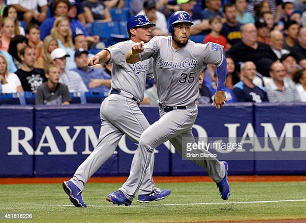 Eric Hosmer of the Kansas City Royals is signaled to go home by third base coach Mike Jirschele of the Kansas City Royals as he scores from second...