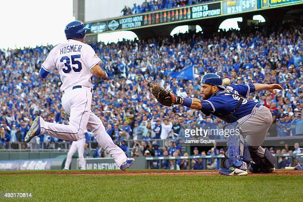 Eric Hosmer of the Kansas City Royals scores a run as Russell Martin of the Toronto Blue Jays is unable to make the tag in the seventh inning during...