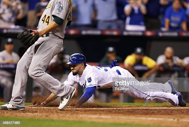 Eric Hosmer of the Kansas City Royals scores on a wild pitch in the eighth inning during their American League Wild Card game against Oakland...