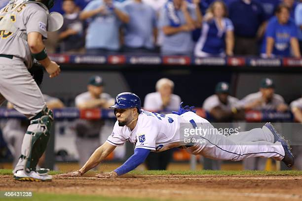 Eric Hosmer of the Kansas City Royals slides into home to score on a single by Christian Colon in the 12th inning against the Oakland Athletics...