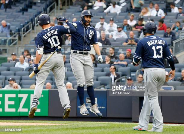 Eric Hosmer of the San Diego Padres celebrates his threerun home run in the first inning with Hunter Renfroe and Manny Machado against the New York...