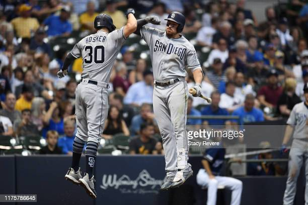 Eric Hosmer of the San Diego Padres celebrates with Hunter Renfroe following a solo home run against the Milwaukee Brewers during the fourth inning...