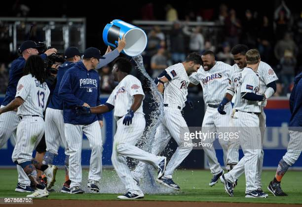 Eric Hosmer of the San Diego Padres has a cooler dumped over him after hitting a walkoff double during the 13th inning of a baseball game against the...