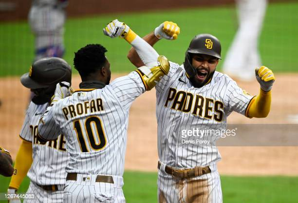 Eric Hosmer of the San Diego Padres is congratulated by Jurickson Profar after hitting a grand slam during the fifth inning of a baseball game...