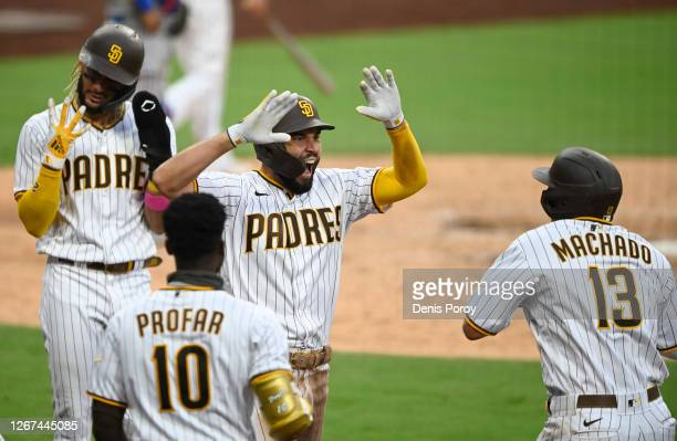 Eric Hosmer of the San Diego Padres is congratulated by Manny Machado after hitting a grand slam during the fifth inning of a baseball game against...
