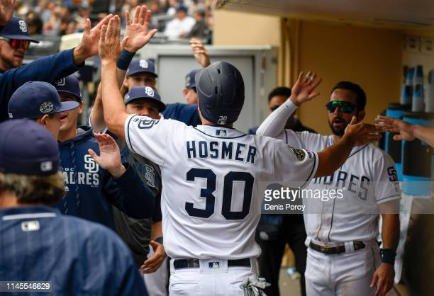 Eric Hosmer of the San Diego Padres is congratulated in the dugout after scoring during the first inning of a baseball game against the Arizona...
