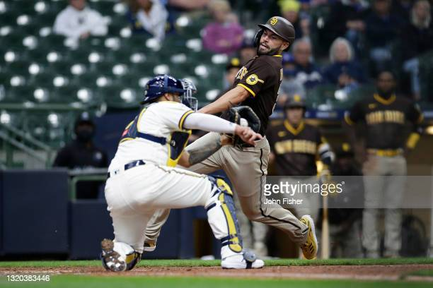 Eric Hosmer of the San Diego Padres is tagged out at home plate by Omar Narvaez of the Milwaukee Brewers in the eighth inning against the Milwaukee...