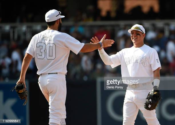 Eric Hosmer of the San Diego Padres left and Luis Urias highfive after defeating the Boston Red Sox 31 in a baseball game at Petco Park August 25...