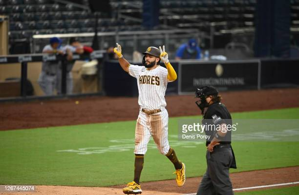 Eric Hosmer of the San Diego Padres points skyward after hitting a grand slam during the fifth inning of a baseball game against the Texas Rangers at...