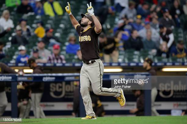 Eric Hosmer of the San Diego Padres raises his arms into the air while rounding third base after hitting a two run homer in the sixth inning against...