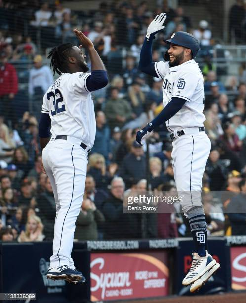 Eric Hosmer of the San Diego Padres right is congratulated by Franmil Reyes after hitting a solo home run during the second inning of a baseball game...