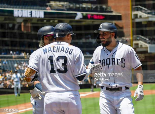 Eric Hosmer of the San Diego Padres right is congratulated by Manny Machado after hitting a tworun home run during the first inning of a baseball...