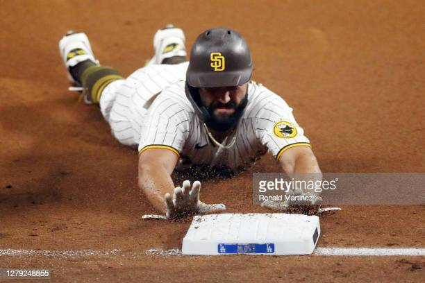 Eric Hosmer of the San Diego Padres slides into third base during the second inning against the Los Angeles Dodgers in Game Three of the National...